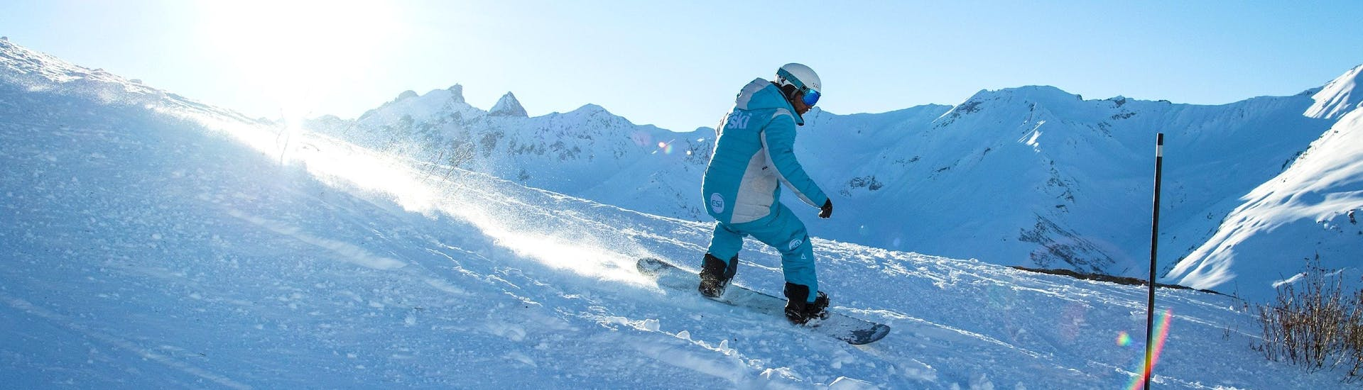 A snowboarder is sliding down a slope during his Private Snowboarding Lessons for All Levels - Midday with the ski school ESI Ski Family in Val Thorens.