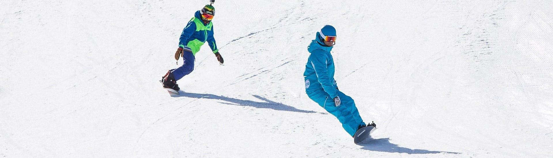 Un snowboardeur suit son moniteur de snowboard de l'école de ski ESI Snow Diam's le long d'une piste enneigée pendant son Cours particulier de snowboard - Notre-Dame de Bellecombe.