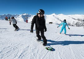A snowboarder is following the instructions from their snowboarding instructor from the ski school ESI Snow Diam's during their Private Snowboarding Lessons - Notre-Dame de Bellecombe.