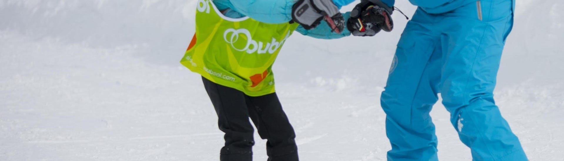 A young snowboarder is learning how to keep their balance on their board with the help of an snowboard instructor from the 333 ski school in Tignes during their Private Snowboarding Lessons - Tignes.