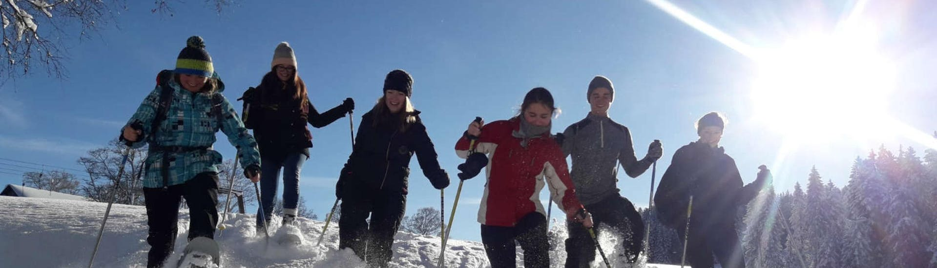 A group of young people is seemingly having fun as they wade through deep powder snow on their private snowshoeing tour with Skischule Schwarzenberg am Bödele.