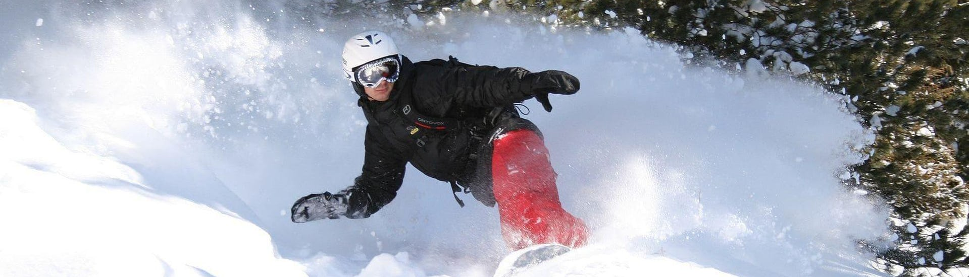 Under the guidance of an experienced instructor form ski school Skischule Arena in Zell am Ziller, a young snowboarder is riding fresh powder during the Private Snowboarding Lessons for Kids & Adults - All Levels.