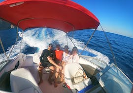 Four friends are enjoying the ride across the Aegean Sea during their Private Speedboat Cruise to the Volcano & Hot Springs with Kamari Beach Watersports Santorini.