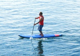 During the private Stand Up Paddle lessons, a man is paddling on the calm waters under the guidance of a certified instructor from Surfaventura.