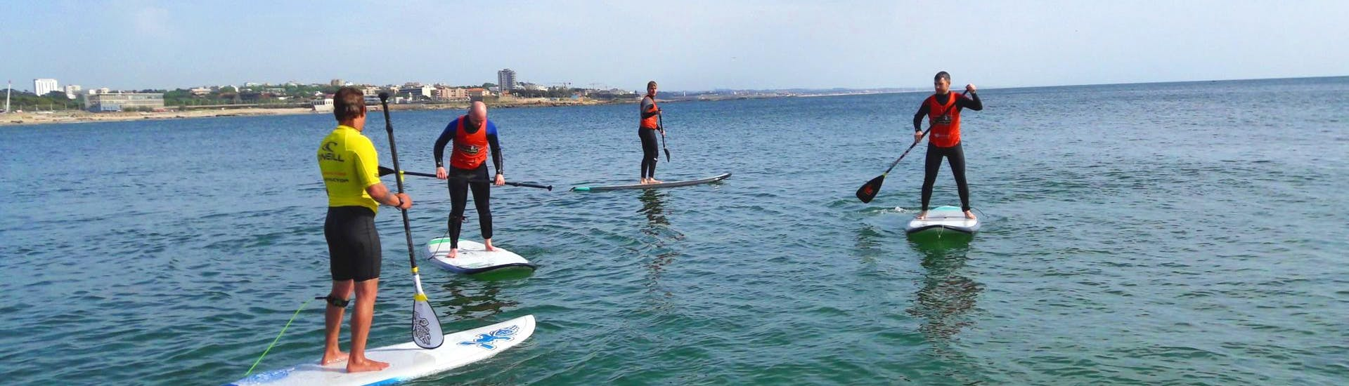 A group of friends is having fun whilst balancing on a SUP during the private Stand Up Paddle lessons organised by Surfaventura.