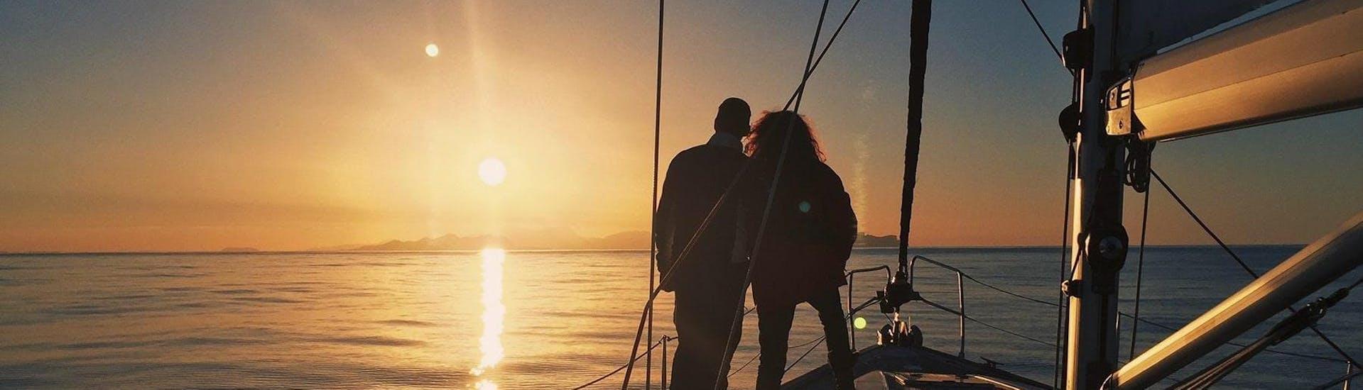 Durante el Tour Privado en Barco de Vela Atardecer con Cena Romántica organizado por Five Star Barcelona, una pareja está disfrutando de los momentos únicos en mar abierto cuando el sol desaparece detrás del horizonte.