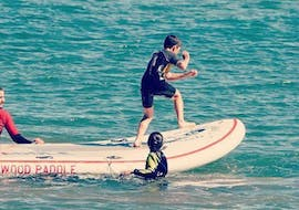 A boy on the SUP is being pushed into the water by his private instructor on his Private Stand Up Paddleboarding course in Jàvea with Anywhere Watersports.