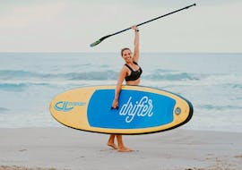 The woman is celebrating her success while punching her fist in the air during her private stand up paddleboarding lesson in Valencia with Anywhere Watersports.