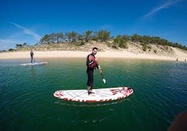 Two participants of the Private SUP Lessons at Lagoa de Albufeira in Sesimbra with Meira Pro Center Sesimbra are paddling in the calm water of the lagoon.