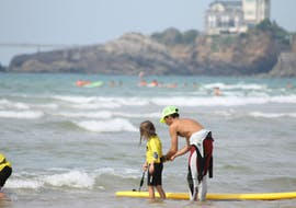 A girl is having private surfing lessons on the Marbella Beach with her instructor of the eco surf school in Biarritz.