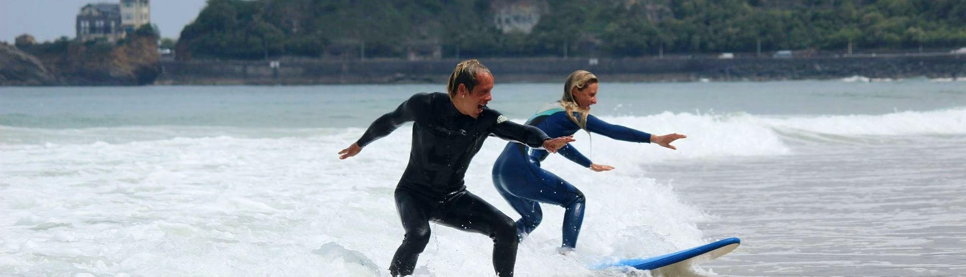 A man is having private surfing lessons on the Marbella Beach with her instructor of the eco surf school in Biarritz.