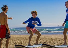 A surf instructor from Mojosurf is teaching two students how to stand correctly on their board during one of the Private Surf Lessons near Byron Bay.