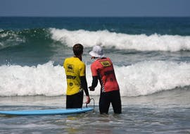 During the private surfing lesson for kids & adults, a certified surf instructor from Arrifana Surf School is advising a young surfer on his technique.