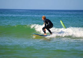 A participants makes his first attempts in the sea under the guidance of a surf instructor from Vilamoura Surf Project during the Private Surfing Lessons at Praia da Falésia for all Levels.
