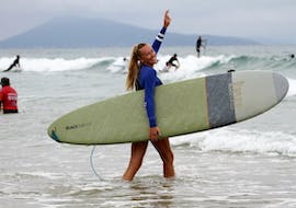 A woman is heading to the waves with her surfboard under her arm, excited to start her Private Surfing Lessons on the Côte des Basques Beach with La Vague Basque.