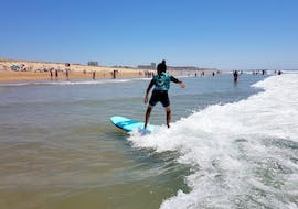 A surfer is taking a small wave on the shore thanks to her private surfing lessons on the Gravière Beach with ESCF Hossegor surf school.