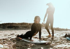 A girls is practicing her stands with an instructor in her private surfing lessons in Valencia with Anywhere Watersports.