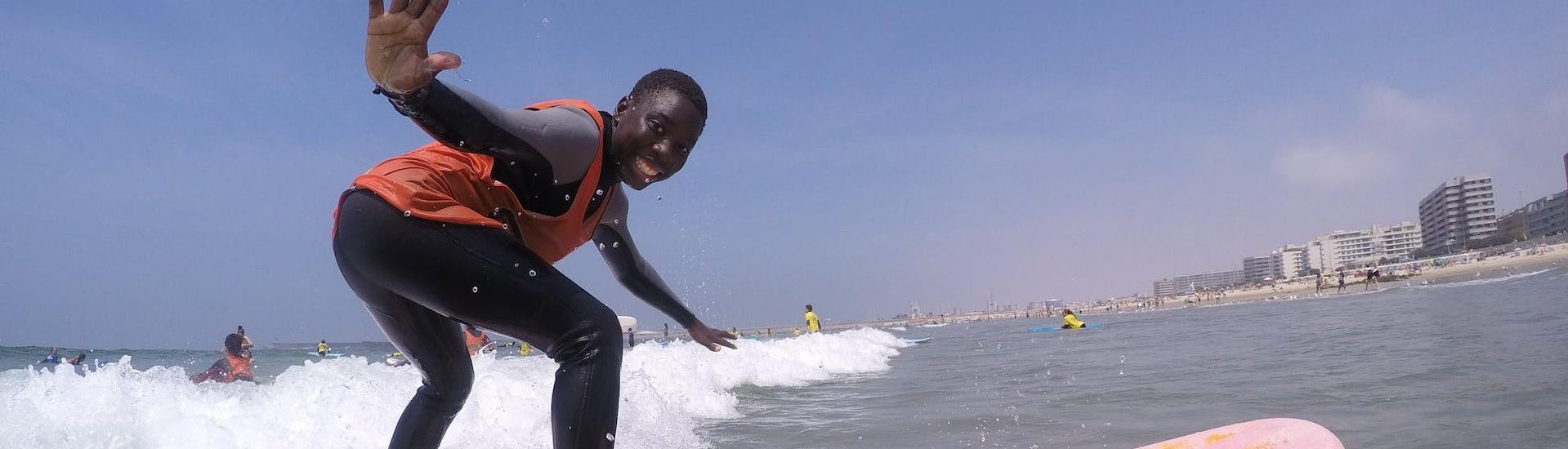 Under the guidance of a certified surf instructor from Surfaventura, a man is having fun whilst riding a big wave during the private surfing lessons on Matosinhos Beach.