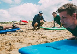 A surf instructor from the surf school ESCF Anglet - Seignoss is giving instructions on the sand to the participants of the Private Surfing Lessons on the Bourdaines Beach.