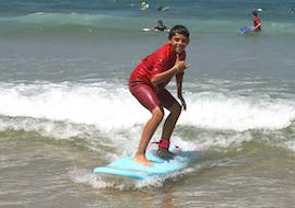 A surfer is happy to stand on his surfboard thanks to his private surfing lessons on the beach of Sablères with the ESCF Vieux Boucau surf school.