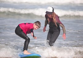 A surf instructor from the surf school ESCF Anglet - Seignosse is supervising a participant while he is surfing in the whitewater on the shore during his Private Surfing Lessons on the Penon Beach.