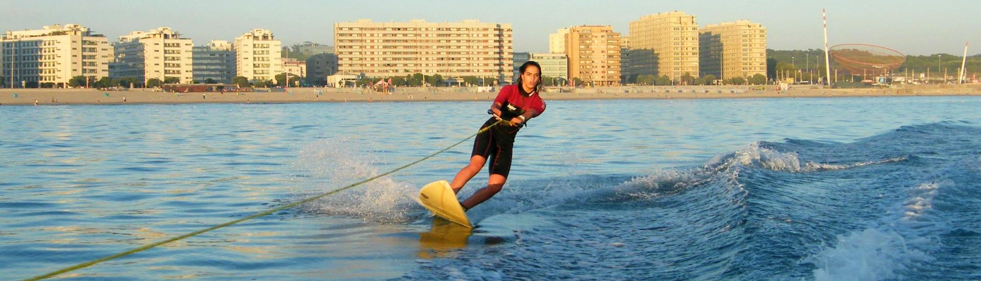 During the private wakeboard & wakesurf lessons, a woman is enjoying wakesurfing under the supervision of a qualified instructor from Surfaventura.