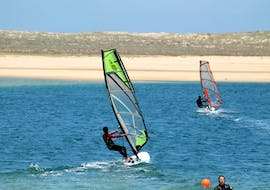During the Private Windsurfing Lessons at Lagoa de Albufeira with Meira Pro Center Sesimbra, a windsurfer is riding over the water of the lagoon.