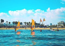 A person is learning to windsurf together with its private instructor during their private windsurfing lessons in Cullera with Anywhere Watersports.