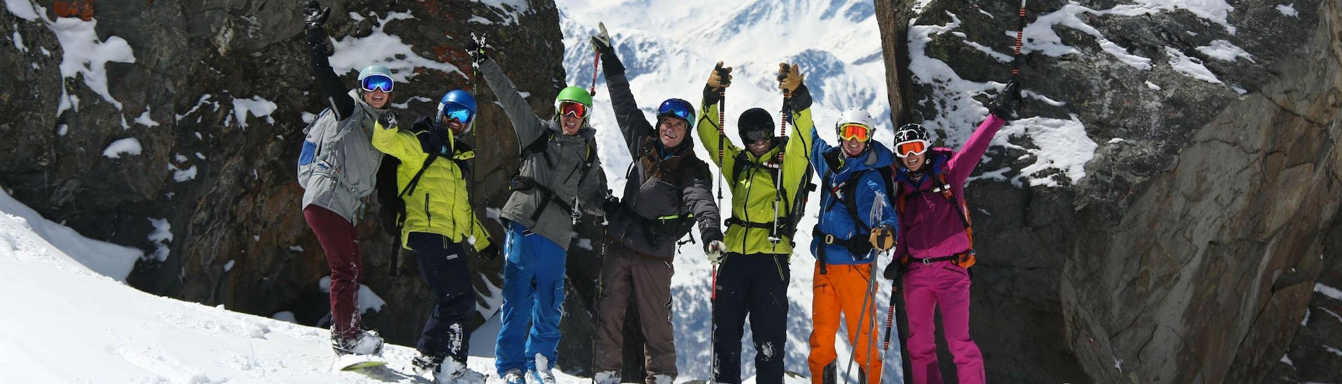 A group of skiers and their ski instructor from Prosneige Méribel are posing together in the snow while enjoying one of their ski lessons.