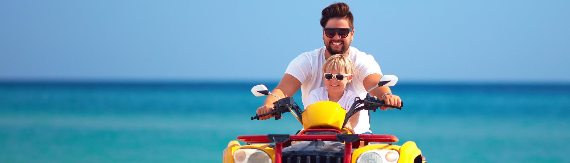 A young dad quad biking with his son in the holiday destination of Sierra de las Nieves.