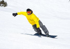 """A snowboarder rides down the sunny slope while enjoying the fresh snow as part of the offer """"Private Snowboarding Lessons for Kids and Adults - Advanced"""" of the snowboard school BOARD.AT."""