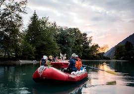 Un groupe de rafteurs savoure un délicieux dîner avec raclette alors que le soleil se couche pendant la sortie rafting & raclette sur le lac de Brienz avec Outdoor Interlaken.