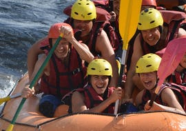 A group is smiling for the photo on their raft during the activity Rafting adventure on the Garonne with H2O vives.