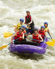 A group of people is trying to keep their boat steady while rafting in Asturias.