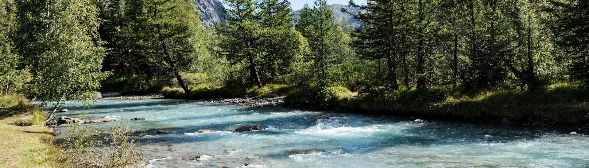 An image of a river flowing through the picturesque mountain scenery that people who go rafting in Aosta Valley get to experience.