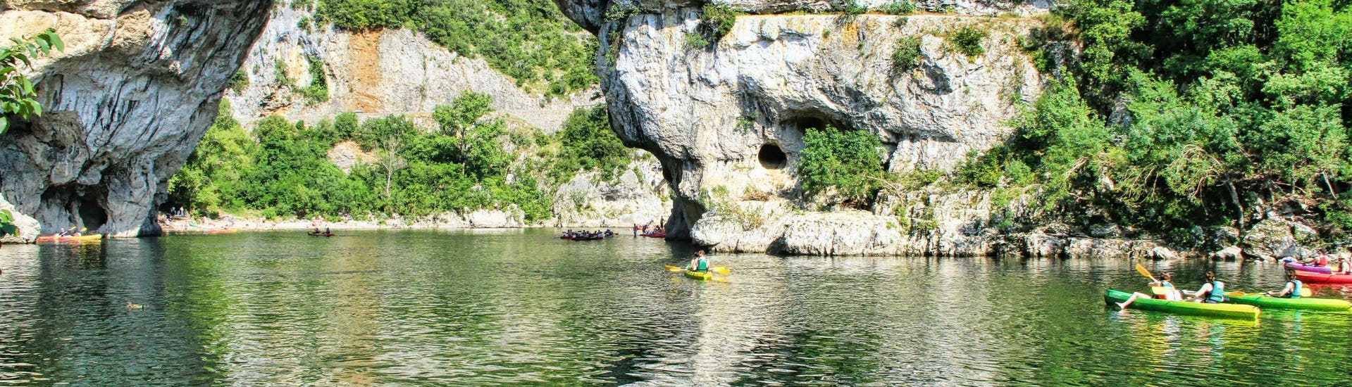 A group of people is paddling through the Pont-d'Arc while canoeing in Ardèche.