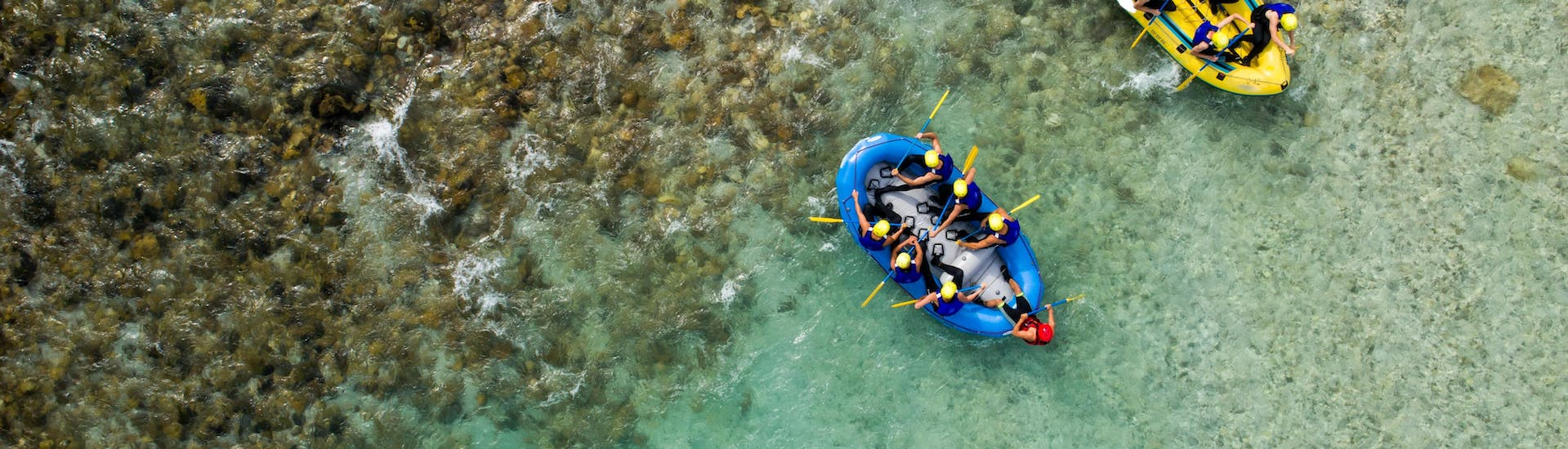 Two groups of people are paddling across the crystal clear waters of the Soca River while rafting in Bovec.