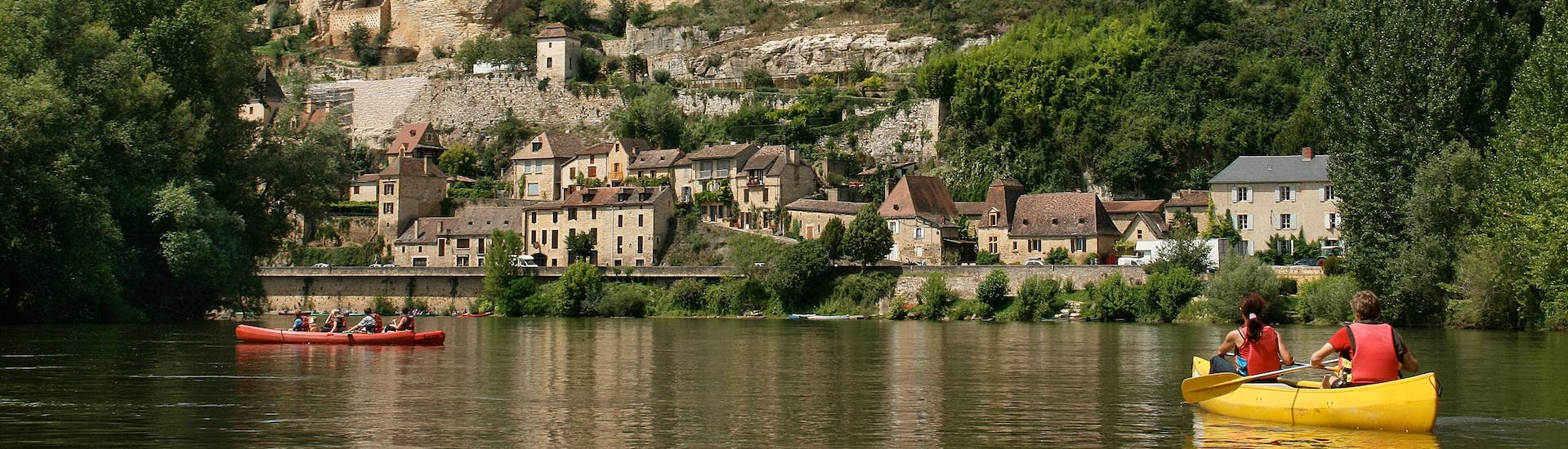 Holidaymakers are taking advantage of their holidays to take a canoe trip on the Dordogne River, and are paddling underneath the Beynac Castle.