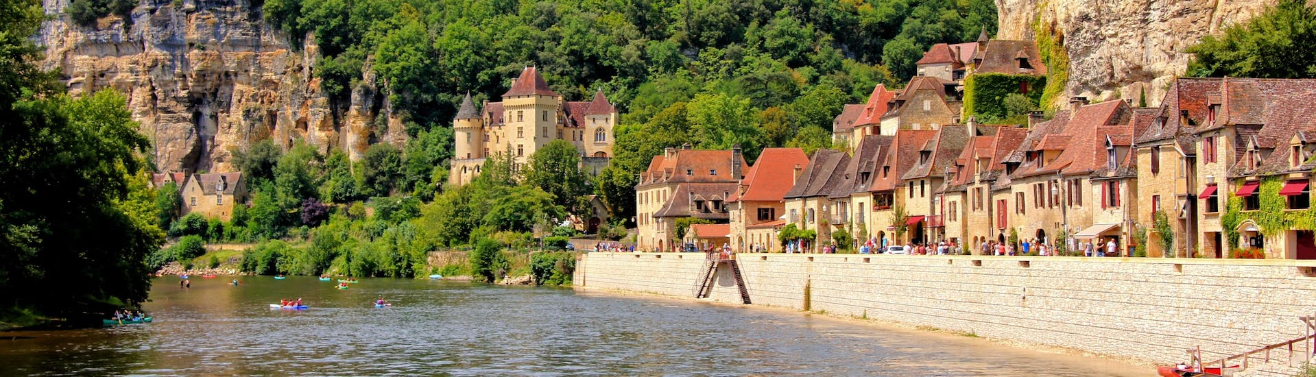 Beautiful view of the village of La Roque-Gageac on the Dordogne River on which tourists tourists do canoeing during summer.