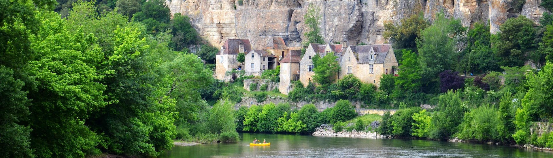 Canoe enthusiasts are paddling quietly on the Vézère river in the Dordogne in front of the troglodytic habitats of the town of Les Eyzies.