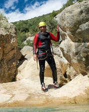 A man is stood on a rock and posing for a photo while canyoning in Mallorca.