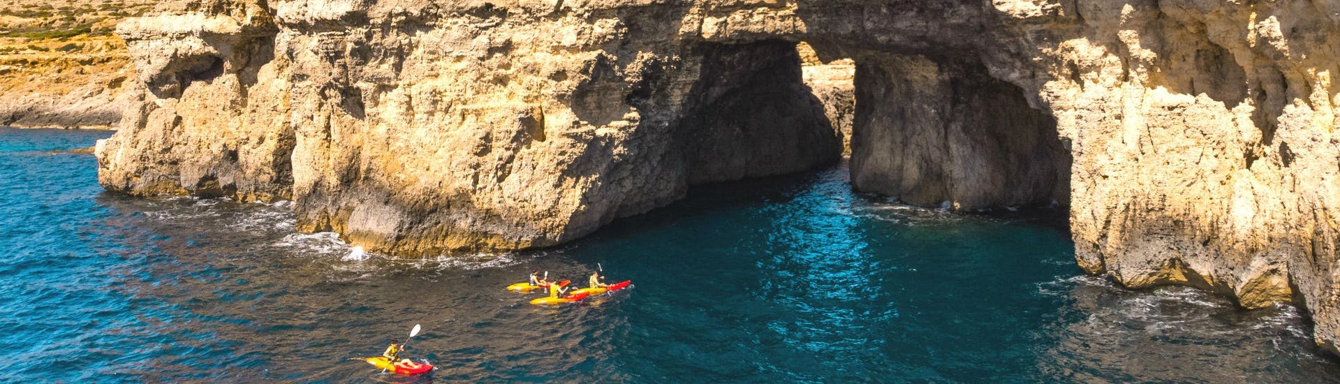 A group of people is paddling into a cave while kayaking in Malta.