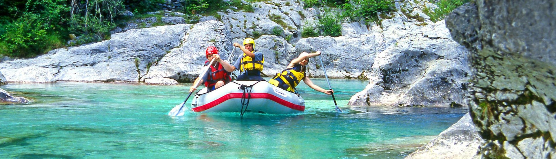 A group of young people enjoying some white water rafting fun in the rafting & canyoning hotspot of Soča Valley .