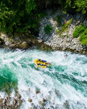 A group of people is pictured from above as they navigate their boat across the rapids while rafting in Valsesia.