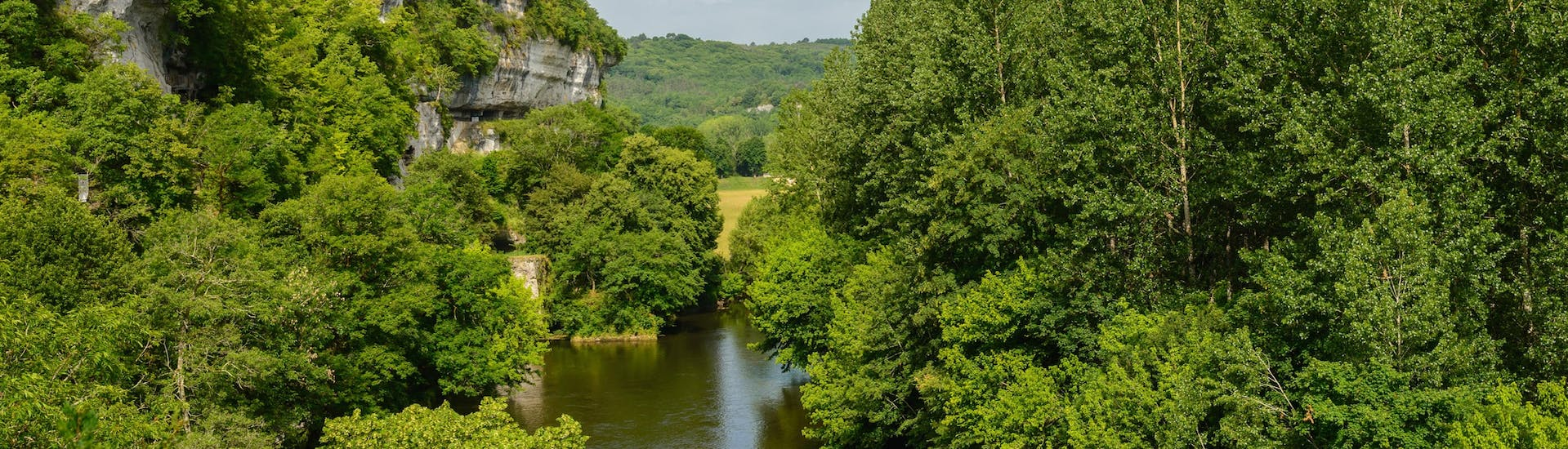 View of the wild Vézère valley in the Dordogne region where tourists enjoy canoeing.