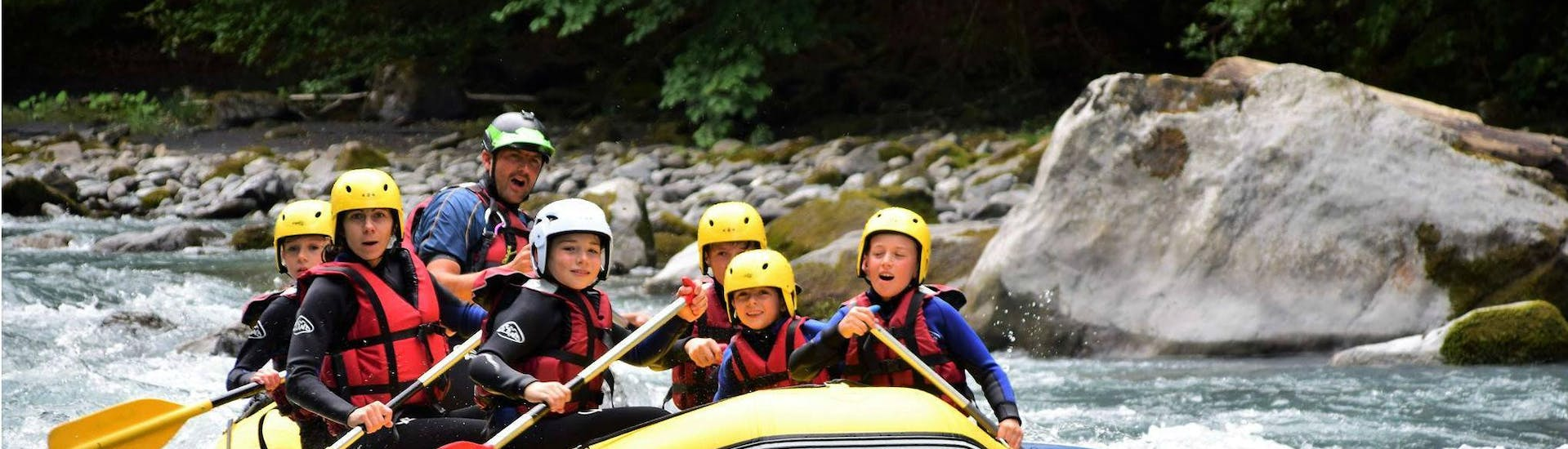 A family is paddling in a beautiful wilderness scenery during their Rafting on Giffre River for Families - Classic with Raft Rider.