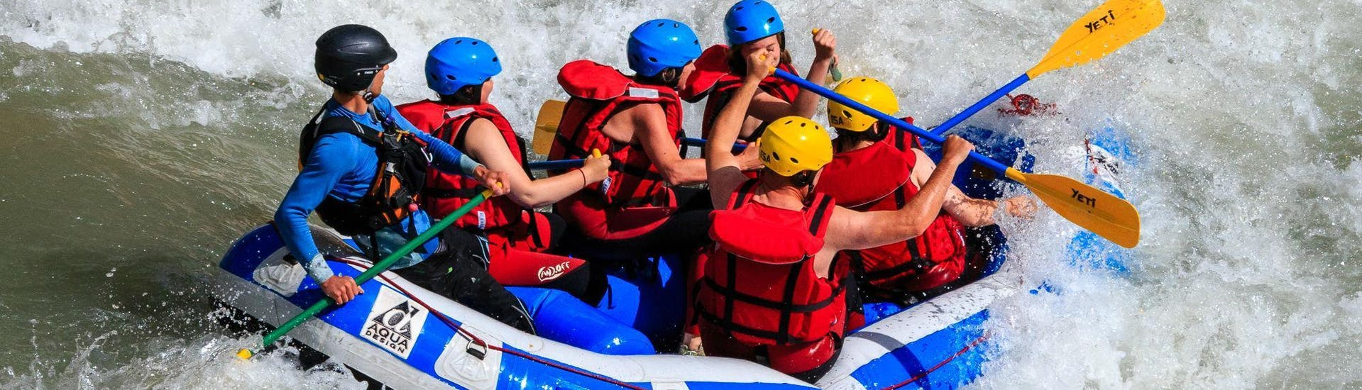 A group of adults and kids are caught in rapids on the Verdon river and are having fun during the Classic rafting descent organized by Yeti Rafting.