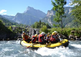 A group of friends is paddling in a beautiful wilderness scenery during their Rafting on Giffre River - Classic with Raft Rider.