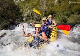 Drei Freunde haben Spaß, während sie beim Rafting auf der Cetina mit Adventure Dalmatia durch eine Stromschnelle paddeln.