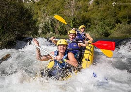 Three friends are having fun as they paddle through a rapid during the Rafting on Cetina River with Adventure Dalmatia.